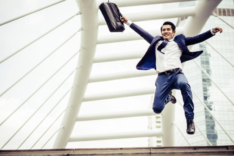 Man holding briefcase jumping in the air