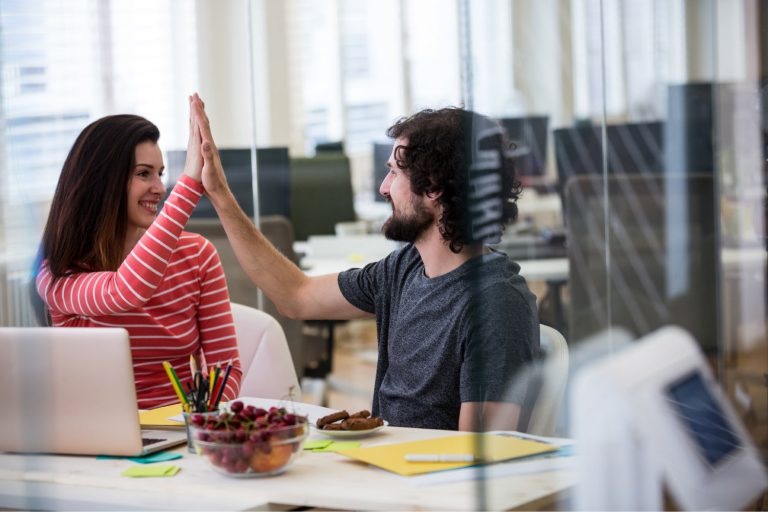 Woman and man high-fiving after achieving success