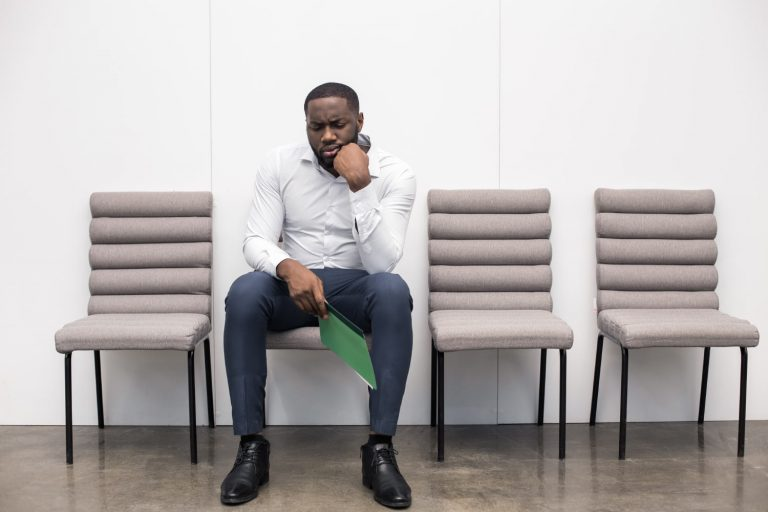 Man sitting on chair sad because he didn't get the job