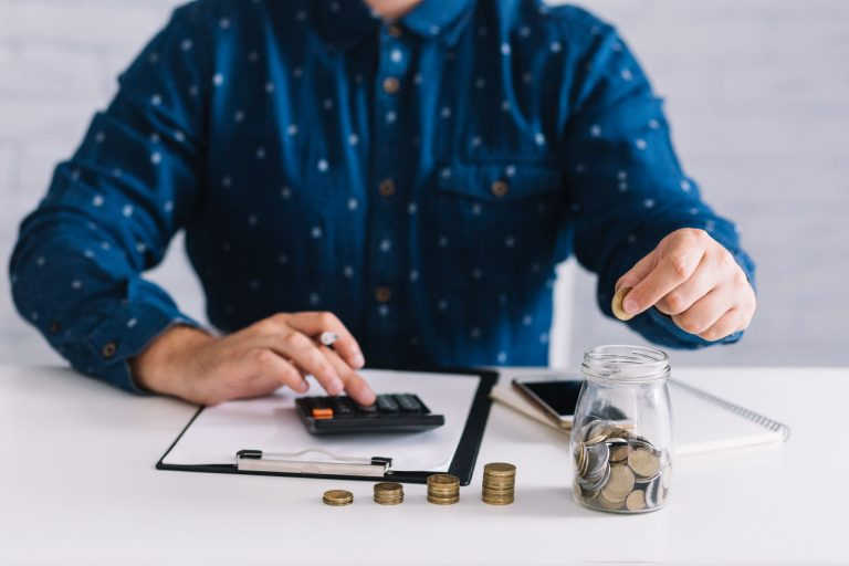 Person at a desk with coins and a calculator working out how to save money