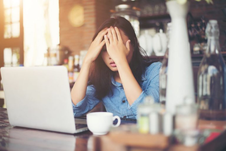 Woman at desk in front of computer with hands on her head feeling stuck