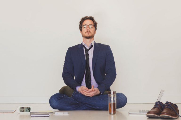 Man in a suit in a meditation pose trying to be calm