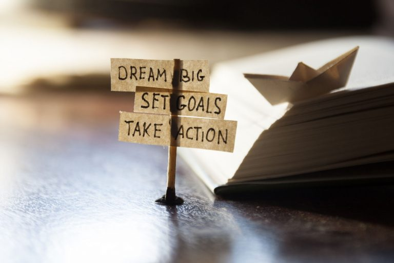 Matchstick holding up paper that says Dream Big, Set Goals, and Take Action