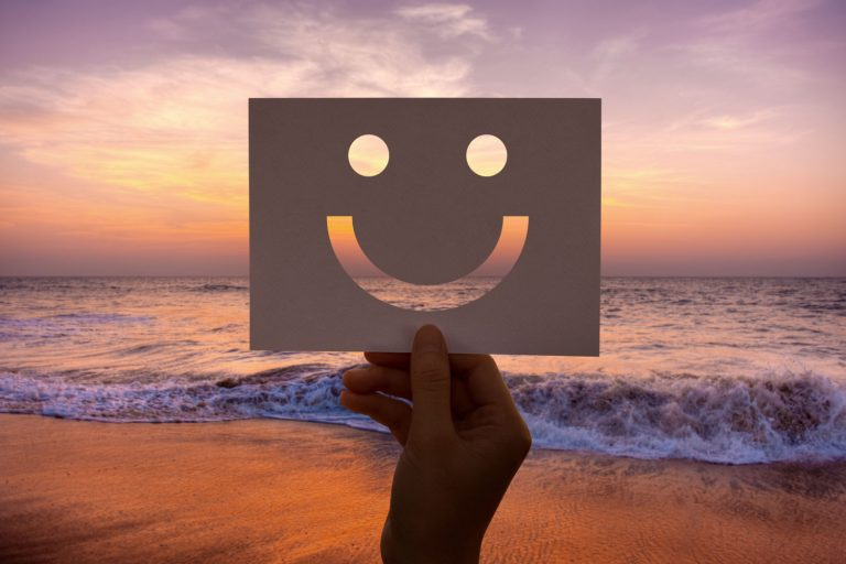 Person's hand holding up a smiley cardboard at the beach, happy to break up life routine