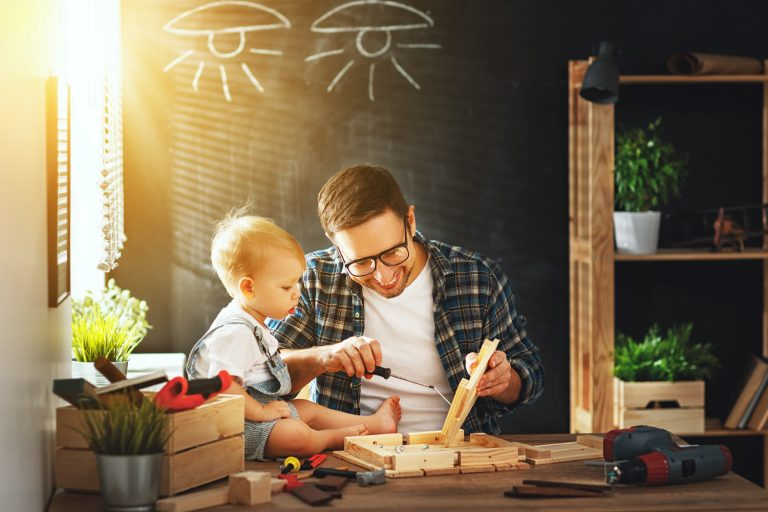 Man at a desk showing his young toddler how to do carpentry