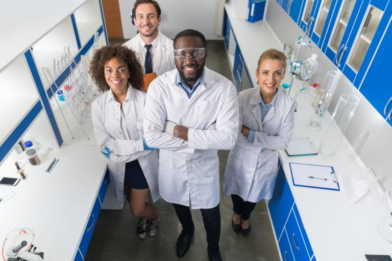 Four scientists in lab coats standing in a laboratory smiling because they're in a science career