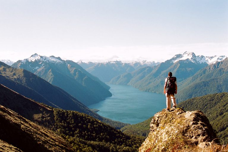 Person standing on mountaintop looking at breathtaking view of water trying to find inspiration