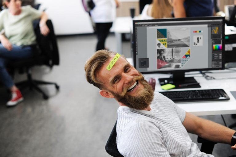 Smiling man with satisfying jobs sitting at a desk at work with post-it that says Be Happy
