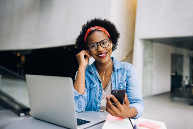 Self-employed woman in front of her laptop with her phone and headphones in her ears