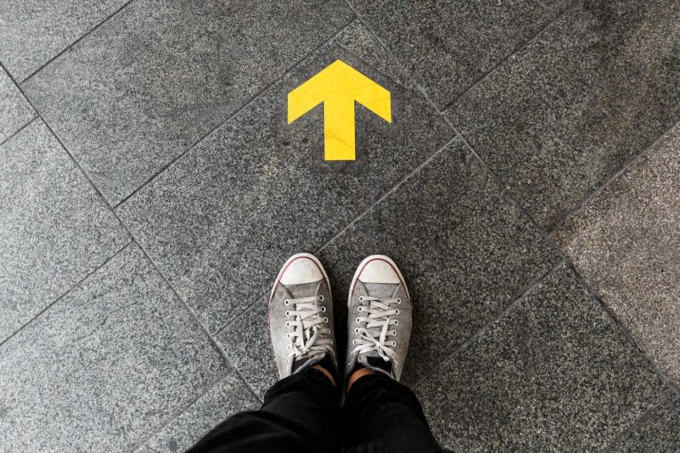Person's feet standing before an arrow pointing forward showing how to get there